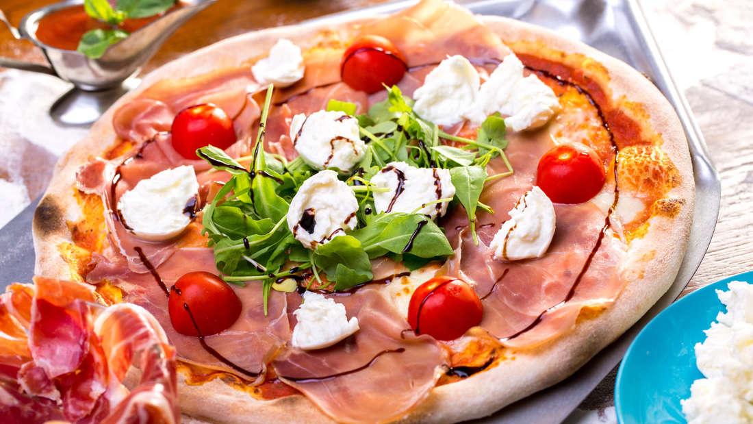 close up of delicious italian pizza with ham, mozzarella, tomatoes and arugula (sebasnoo)