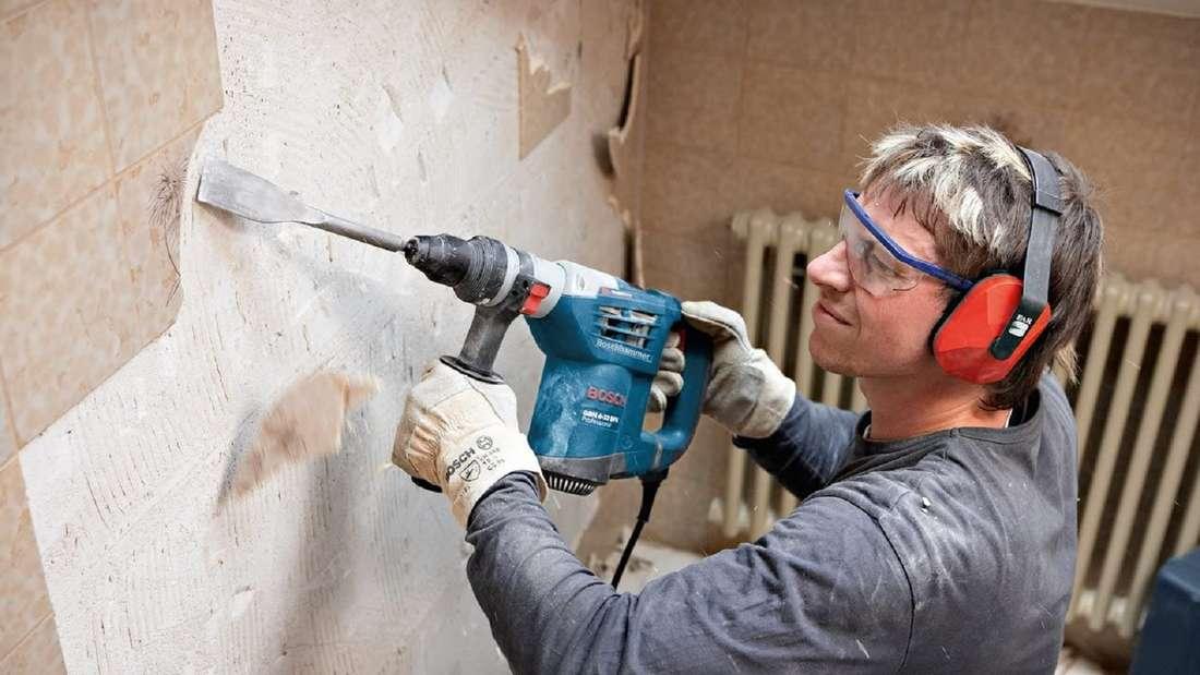 Handwerker benutzt einen Bosch Bohrhammer, um Fließen von einer Wand zu entfernen