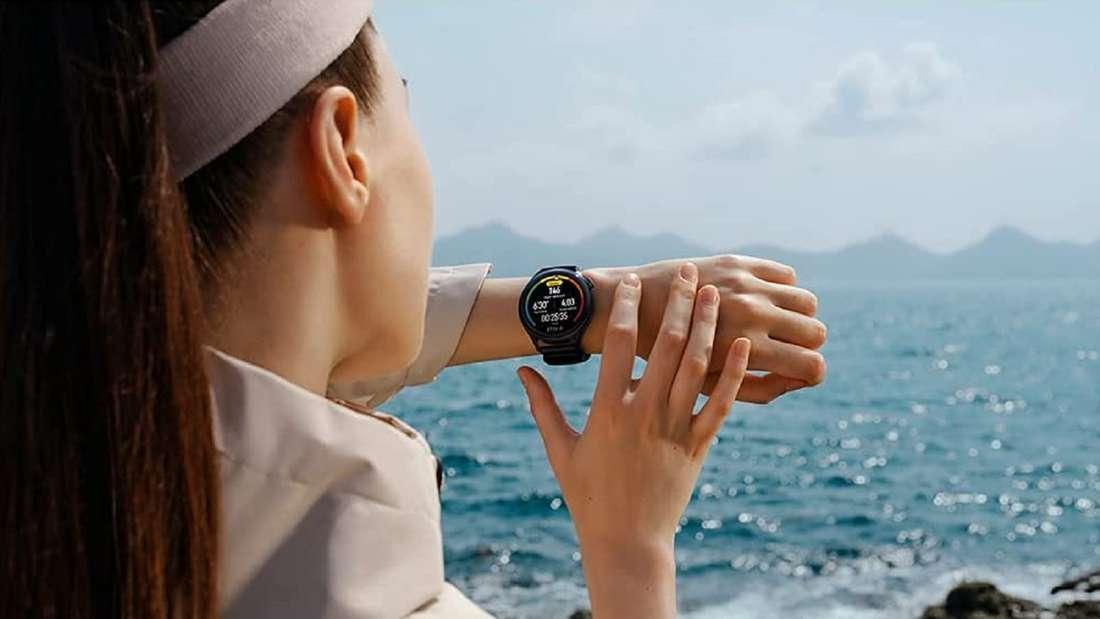 Eine Frau steht an einer Küste und schaut auf ihre Huawei Smartwatch am linken Handgelenk.